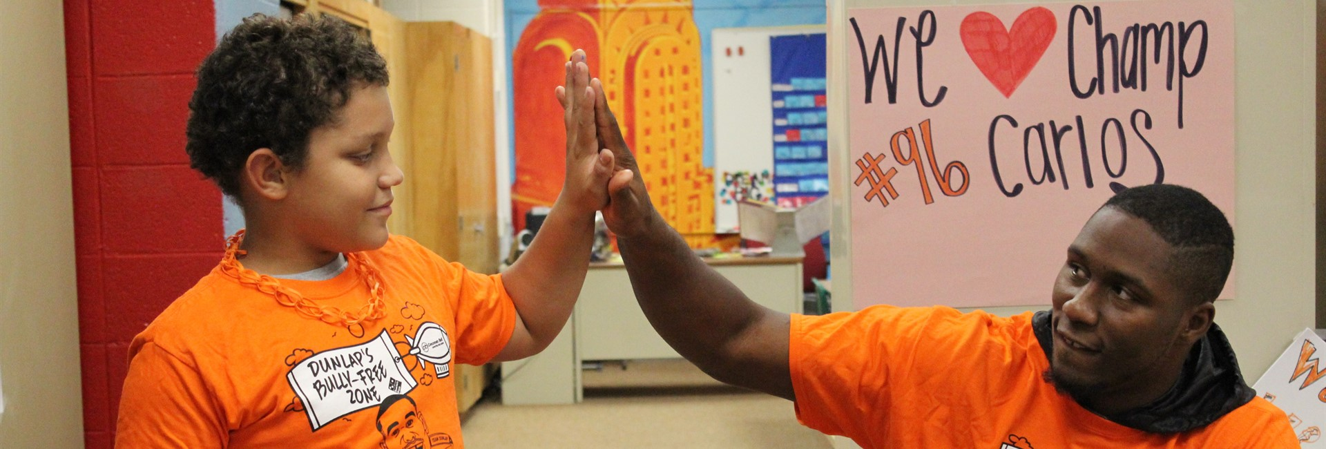 Latonia student gives Carlos Dunlap a high five.